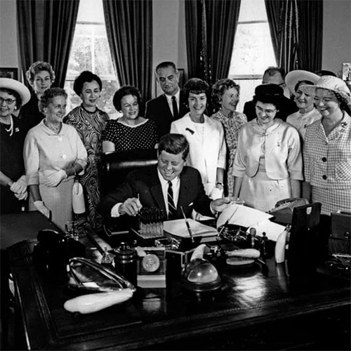 The President's Pens - American Association of University Women members with President John F. Kennedy as he signs the Equal Pay Act into law